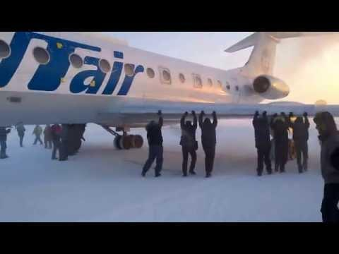 Passengers pushing own aircraft in Siberia